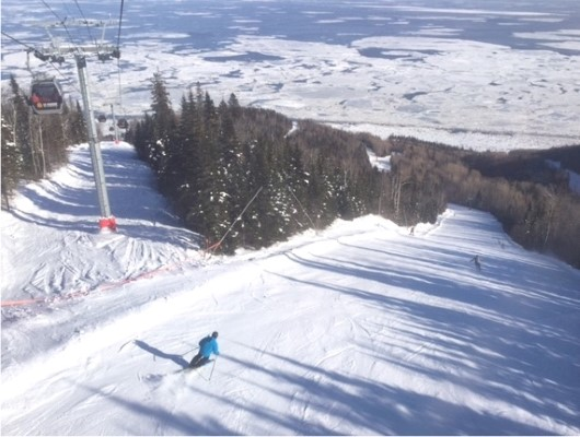 Skiers enjoy one of the several grand trails at LeMassif that descend down to the frozen St Lawrence.